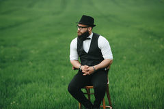 Man with a beard. A man with a beard sitting on a chair on the field Royalty Free Stock Image