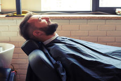 Man with beard sitting on chair Stock Photo