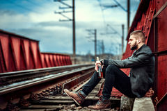 Man with beard sitting on the railway. Young man with beard sitting on the railway Royalty Free Stock Images