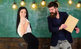 Man with beard slapping student, chalkboard on background. Girl on helpless face punished by teacher. Schoolmaster. Punishes student with slapping on her royalty free stock photography