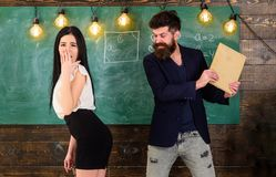 Man with beard slapping student, chalkboard on background. Schoolmaster punishes student with slapping on her. Buttocks. Girl on guilty and helpless face royalty free stock photography