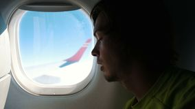 Man with the beard is sleeping near the window of the plane during the flight stock footage