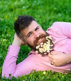 Man with beard on smiling face enjoy nature. Bearded man with daisy flowers lay on meadow, lean on hand, grass. Background. Masculinity concept. Hipster with royalty free stock photo