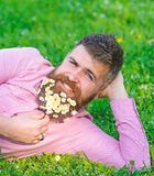 Man with beard on smiling face enjoy nature. Bearded man with daisy flowers lay on meadow, lean on hand, grass. Background. Masculinity concept. Hipster with stock photography