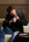Man with a beard smokes a cigar Stock Images