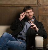 Man with a beard smokes a cigar Stock Photo