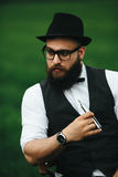 Man with a beard smokes electronic cigarette Stock Photography