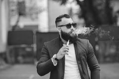 Man with a beard smokes electronic cigarette Royalty Free Stock Photos