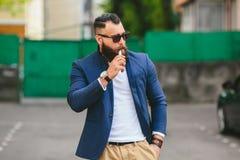 Man with a beard smokes electronic cigarette Stock Image