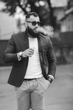 Man with a beard smokes electronic cigarette Royalty Free Stock Photography