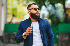 Man with a beard smokes electronic cigarette Stock Photos