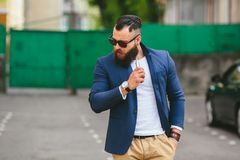 Man with a beard smokes electronic cigarette. Well dressed man with a beard smoking electronic cigarette Royalty Free Stock Image