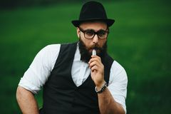 Man with a beard smokes electronic cigarette Royalty Free Stock Images