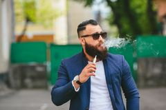 Man with a beard smokes electronic cigarette Stock Image