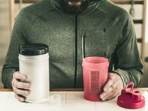 Man with a beard sports clothes holds a jar of protein and a shaker, against the backdrop of sports equipment a sporty lifes stock images