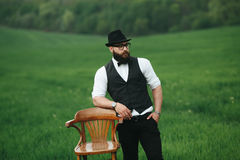 Man with a beard. A man with a beard is standing near the chair on the field Stock Images