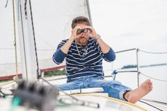 Man sits on sailing yacht and looks through binoculars Royalty Free Stock Image