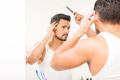 Man with a beard styling his hair. Portrait of a handsome young man with a beard using a comb to style his hair in front of a bathroom mirror Royalty Free Stock Photos