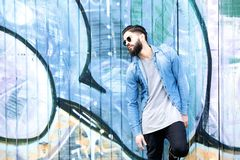 Man with beard and sunglasses. Portrait of a young man with beard and sunglasses relaxing against graffiti background outdoors Royalty Free Stock Image