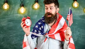 Man with beard on surprised face holds flag of USA and clock, chalkboard on background. American teacher with american. Flags holds alarm clock. American Royalty Free Stock Photos
