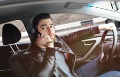 Young man talking on the phone while driving a car. A man with a beard talking on a mobile phone in the car Stock Images