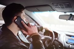 Young man talking on the phone while driving a car. A man with a beard talking on a mobile phone in the car Royalty Free Stock Images