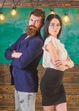 Man with beard and teacher in eyeglasses stand back to back, chalkboard on background. School staff concept. Lady and stock image