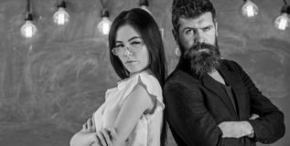 Man with beard and teacher in eyeglasses stand back to back, chalkboard on background. Teamwork concept. Lady and. Hipster working together in school. Teacher stock image