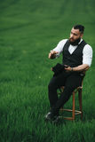 Man with a beard, thinking in the field near chair Stock Images