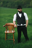 Man with a beard, thinking in the field near chair Royalty Free Stock Photos