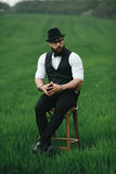 Man with a beard, thinking in the field near chair Royalty Free Stock Images