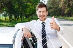 Man with beard thumbing up near car Stock Image