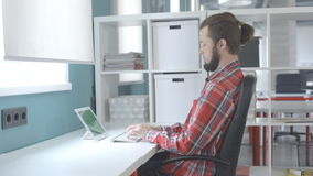 A man with a beard and top knot sits close to chair in office and typing on wireless keyboard. Working web-programmer is directly connected to global network stock video footage