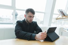 A man with a beard uses a tablet in a beautiful light cafe. A businessman looks at the tablet at a lunch break. Stock Image