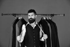 Man with beard by clothes rack. Designer takes measures. Man with beard in vest by clothes rack. Designer takes measures near clothes hangers. Tailor with stock photo
