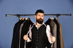 Man with beard by clothes rack. Designer takes measures. Man with beard in vest by clothes rack. Designer takes measures near clothes hangers. Tailor with royalty free stock photos
