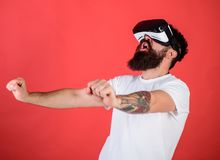 Man with beard in VR glasses driving motorbike, red background. Hipster on excited face driving bike on high speed in royalty free stock photography