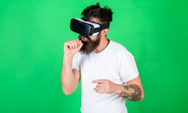 Man with beard in VR glasses, green background. Guy with VR glasses singing with imaginary microphone. Hipster on busy stock photo