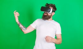 Man with beard in VR glasses, green background. Hipster guitarist on enthusiastic face use modern technology for. Entertainment. Guy with VR glasses learn to stock images