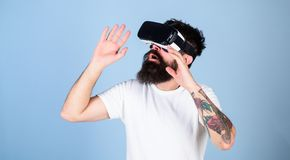 Man with beard in VR glasses, light blue background. VR gadget concept. Guy with head mounted display interact in. Virtual reality. Hipster on busy face stock image