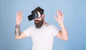 Man with beard in VR glasses, light blue background. Hipster on busy face exploring virtual reality with modern gadget. VR gadget concept. Guy with head royalty free stock images