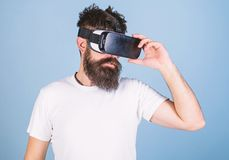 Man with beard in VR glasses, light blue background. Hipster on serious face use modern gadget to explore virtual. Reality. VR gadget concept. Guy with head stock image