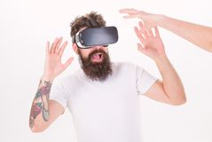 Man with beard in VR glasses, white background. Virtual reality concept. Guy with head mounted display interact with. Hand in virtual reality. Hipster use stock photography
