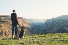 A man with a beard walking his dog in the nature, standing with a backlight at the rising sun, casting a warm glow and Royalty Free Stock Images