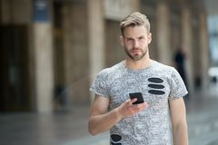 Man with beard walks with smartphone urban background. Guy use smartphone to send message or find location. Man use. Navigation option to get to destination royalty free stock image