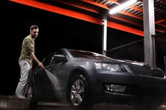 A man with a beard or car washer washes a gray car with a high-pressure apparatus at night in a car wash stock image