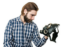The man with beard watching at a gas mask Stock Images