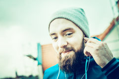 Man with a beard, wearing a hat and smiling with headphones  the urban background blurred landscape Royalty Free Stock Images