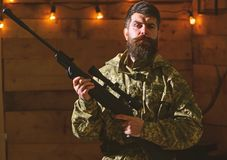 Man with beard wears camouflage clothing in wooden interior background. Gamekeeper concept. Hunter, brutal hipster with. Gun in his hand ready for hunting royalty free stock images