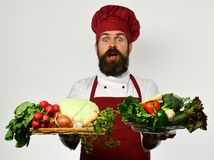 Man with beard on white background. Cook with surprised face. In burgundy uniform holds salad ingredients. Chef holds board with fresh vegetables on board and Stock Photo